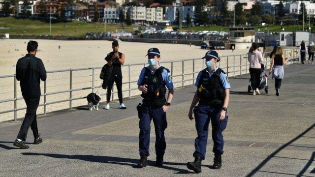 شرطيان يمران بأشخاص خرجوا من منازلهم لممارسة الرياضة