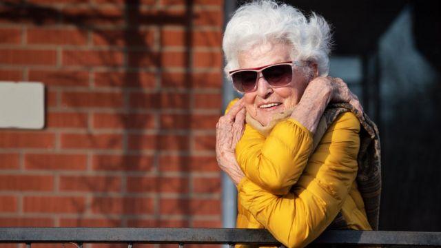 زن مسنی خود را در آغوش گرفته