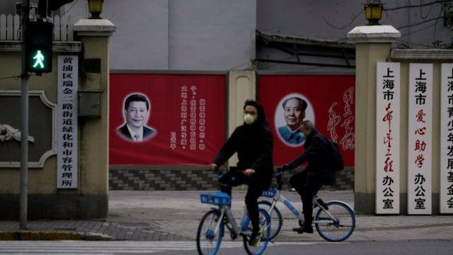 Gente con mascarillas pasando al lado de retratos de Xi Jinping y de Mao Zedong.