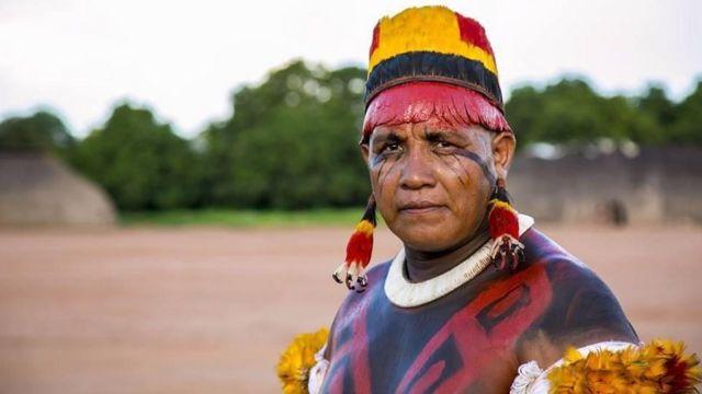 Yanamá Kuikuro, um homem indígena com adereços tradicionais de seu povo, ao ar livre