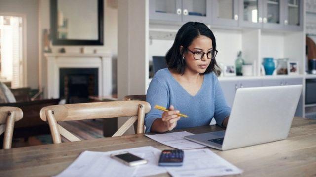 Una mujer trabaja desde la sala de su casa.