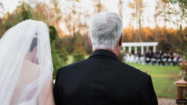 Pai e noiva de costas, indo em direção ao altar em jardim