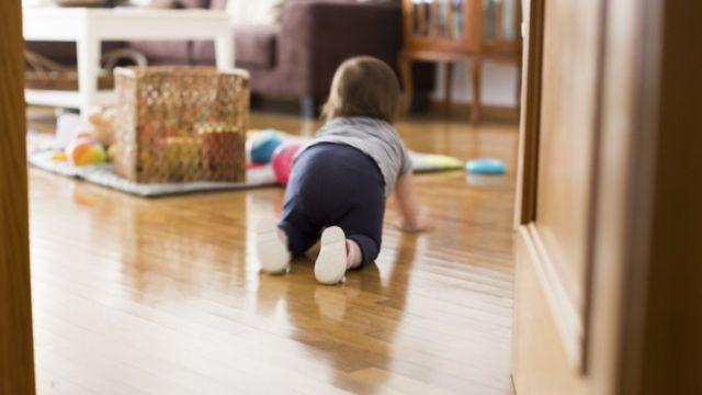 Bebé gatea hacia los juguetes.