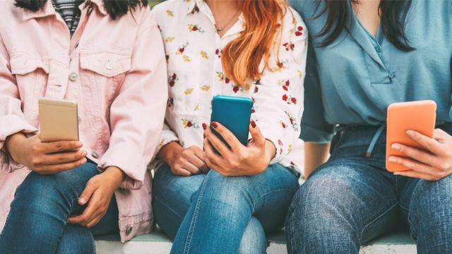 Friends using mobile smart phones outdoor
