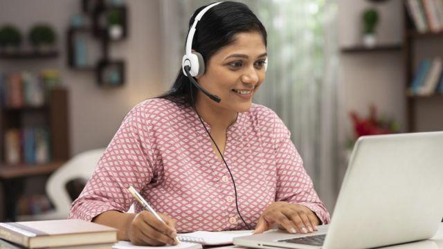 Una mujer conectada a una computadora.