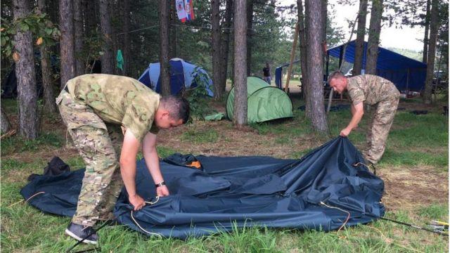 Ruski instruktori Evgenij i Alekej sklapaju šator nakon što je policija zatvorila kamp