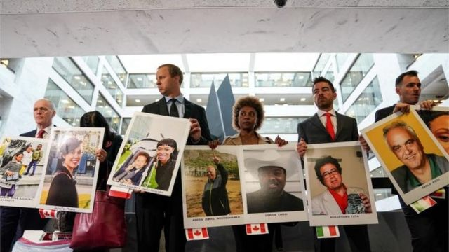 Family members hold photographs of Boeing 737 MAX crash victims lost in two deadly 737 MAX crashes