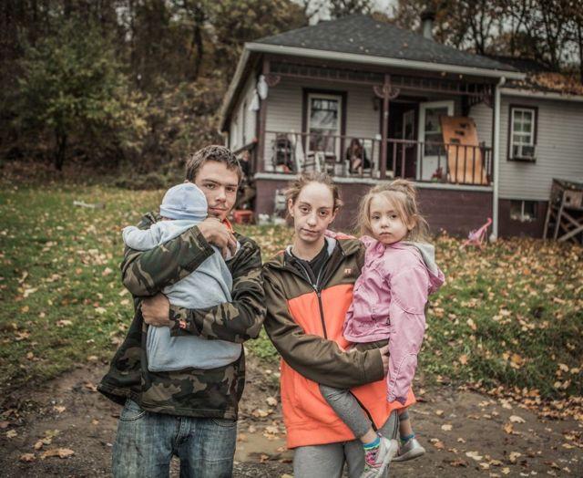 Greg y Ellen holding con sus dos hijos frente a una casa