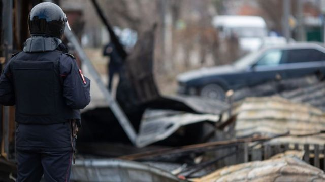 полицейский и разрушенный дом