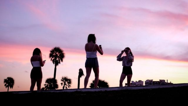Young people take photos in the sunset