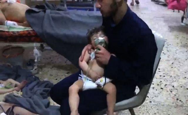 یک امدادرسان در حال نگه داشتن گاز اکسیژن برای کودکی است که گفته میشود در حمله دیروز مسموم شده است