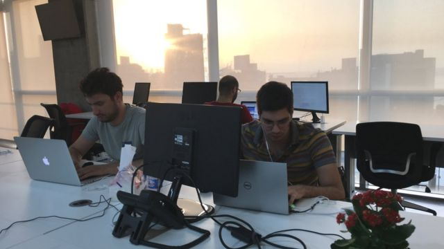 Two young men working at computers with the sunsetting out of the window of the skyscraper