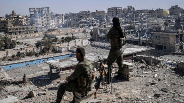 시리아민주군(SDF)가 지붕 위에서 IS로부터 탈환한 락까를 바라보고 있다.