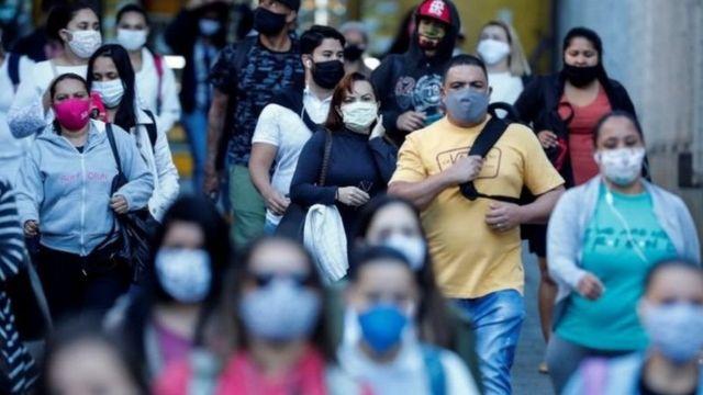 Grande quantidade de pessoas caminha, com máscaras, em cidade brasileira