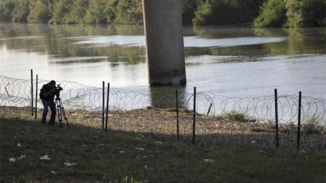Alambre de púas en la orilla del río.