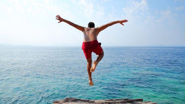 Hombre saltando al océano