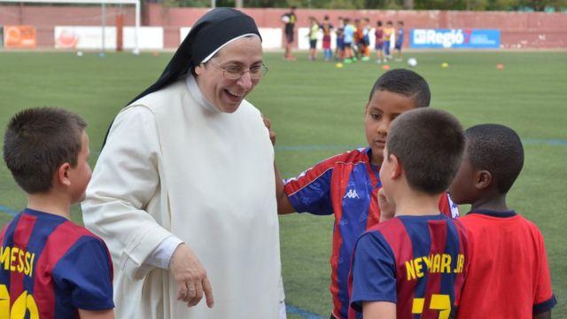 Sor Lucía rodeada de niños en un partido de fútbol.