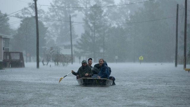 Лодка с волонтерами плывет по одной из затопленных улиц