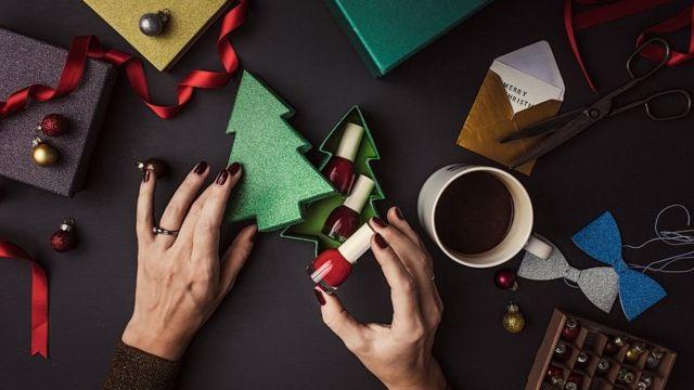Woman packing nail polish into a pretty gift-box, shaped like a glittery Christmas Tree