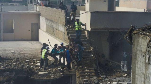 Imagem mostra residentes ajuando a retirar uma pessoa dos escombros