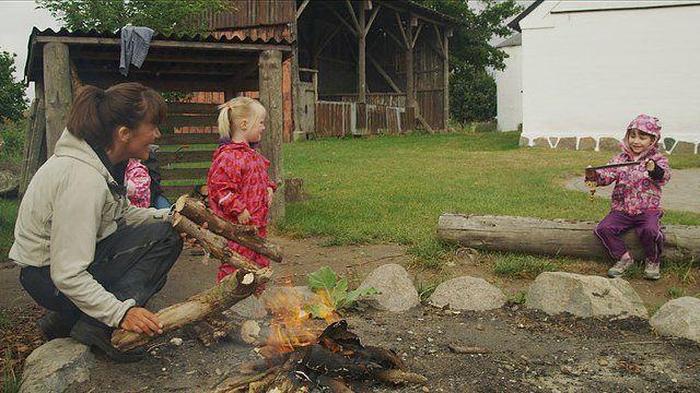 """Crianças perto de fogueira em cena do documentário """"Nature Play"""""""