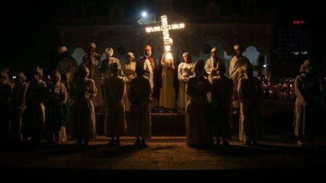 Oração com cruz iluminada