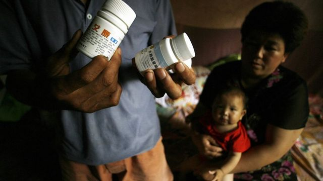 AIDS sufferers Cao Xiaonian (L) shows his medicine whilst his wife Zhou Xiaoneng (R) holds their 9-month-old baby in their village home in China's southern Henan province 02 August 2006