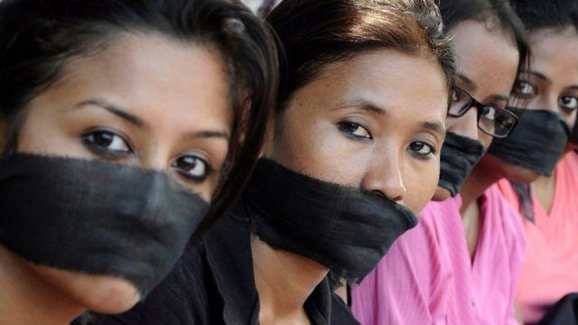 Miembros de una asociación de fotoperiodistas con bandas negras en la boca, protestan por la violación de una colega.