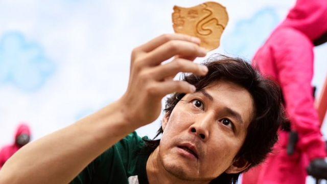 Seong Gi-hun, um dos personagens principais de 'Round 6', segura uma dalgona