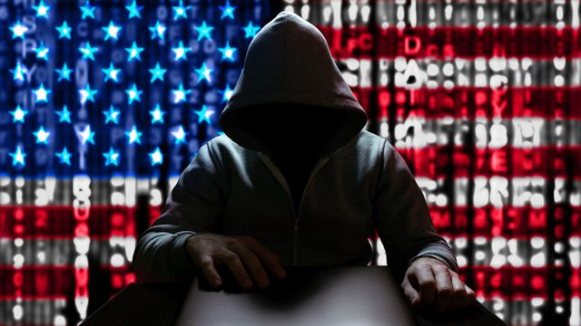 A hacker with the USA flag in the background