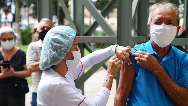 Enfermeira aplicada vacina no braço de homem