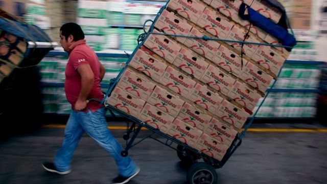 Hombre cargando cajas en el mercado de abastos en Ciudad de México