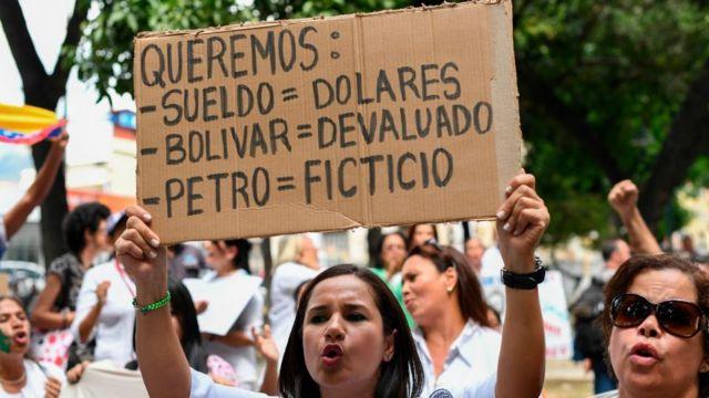 Manifestante segura placa que diz: 'Queremos: Salário = Dólares; Bolívar = Desvalorizado; Petróleo = Fictício'