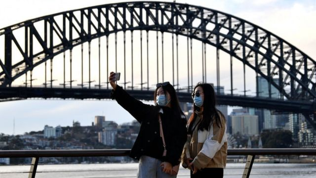 Chinese people wearing masks take a selfie in front of the Sydney Harbour Bridge
