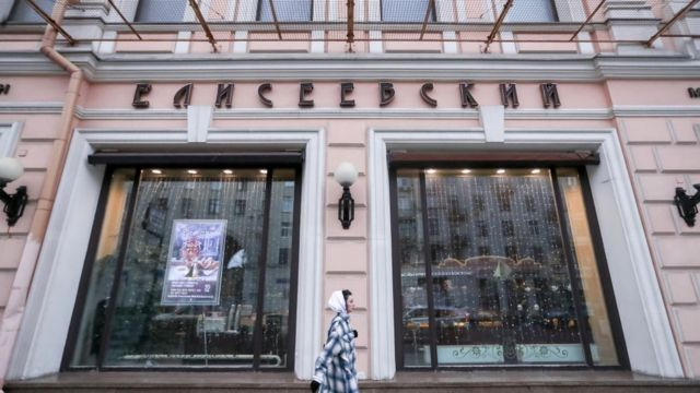 25 de novembro de 2020: mulher passa pela mercearia Yeliseyevsky na rua Tverskaya, centro de Moscou