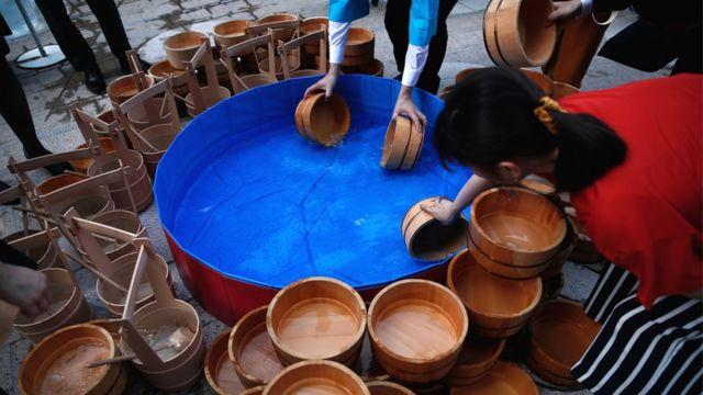 通りの温度を下げるため、打ち水をしようと木桶で水をすくう人たち