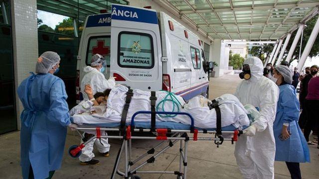 Profissionais da saúde levam paciente numa maca