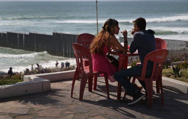 Pareja en Tijuana, en el punto más occidental de la frontera entre México y Estados Unidos, con el muro que divide ambos países detrás.