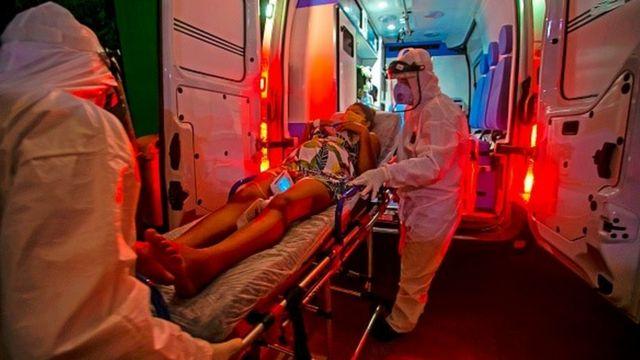 Profissionais de saúde levam mulher em maca para dentro de uma ambulância
