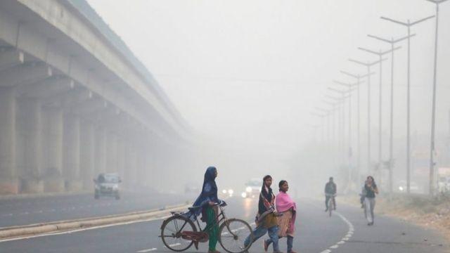 Mujeres cruzan una calle de Nueva Delhi casi sin visibilidad.