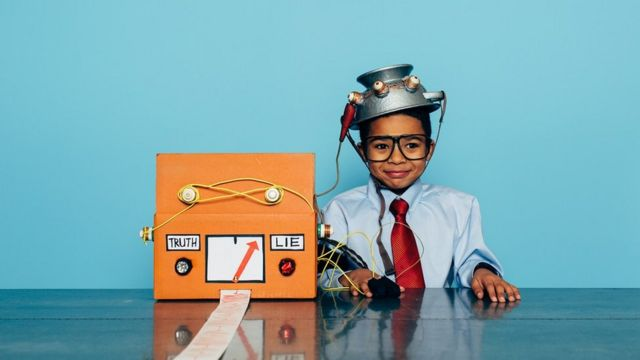 """A child dressed up as a businessman, with a homemade """"lie detector"""" fashioned from a cardboard box"""
