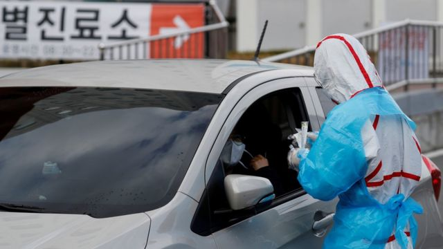 A medical staff member in protective gear prepares to take samples from a driver at one of South Korea's drive-through testing centres in Daegu, 3 March 2020