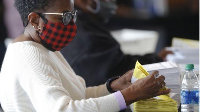 Mulher manuseando votos nos Estados Unidos