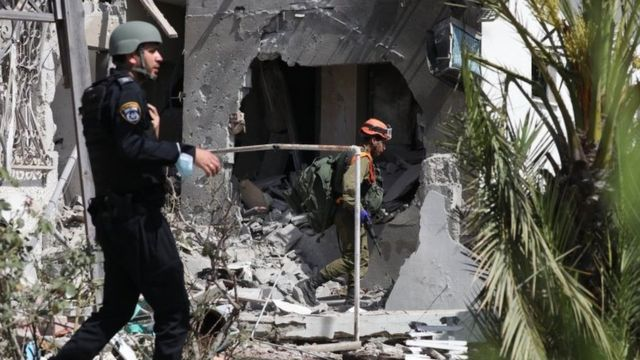 Israeli security forces inspect a home in the city of Ashkelon that was hit by a rocket fired from the Gaza Strip (11 May 2021)