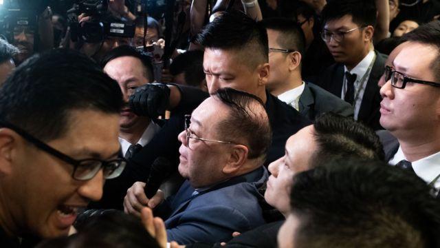石禮謙在建制派議員護送下進入會議室,泛民主派議員阻止他前往主席台。