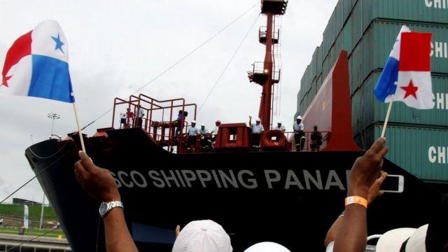 Varias personas sostienen banderas frente a un buque atracado en el canal de Panamá.