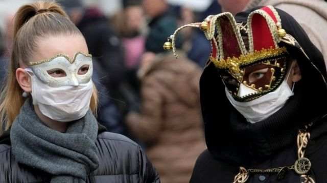 Masked carnival revellers wear protective face masks at Venice Carnival