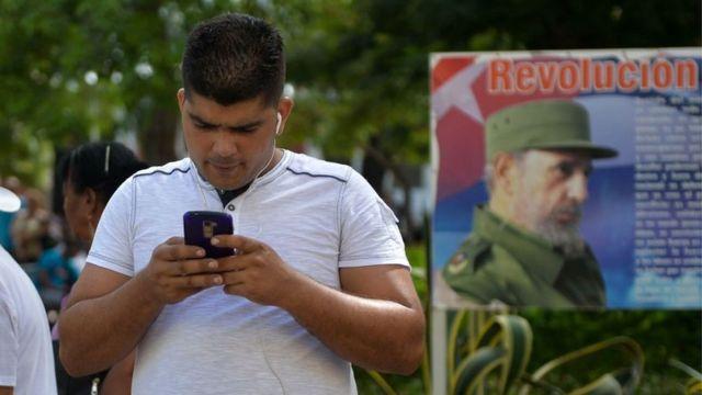 Cubano usando celular