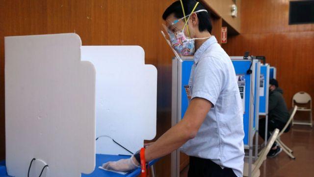 Hombre votando con mascarilla facial.