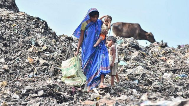Uma mulher carrega seu filho em um depósito de lixo na Índia